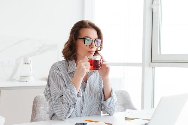Mooie onderneemster in vrijetijdskleding die hete thee drinkt terwijl het zitten en het rusten na administratie thuis