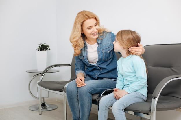Mooie ondersteunende jonge moeder die naar haar kind kijkt en ervoor zorgt dat ze niet erg nerveus is voor het bezoek aan een dokter