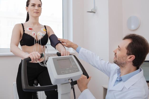 Mooie ongelooflijke bekwame cardioloog die de tonometer repareert terwijl een vrouw enkele oefeningen doet om mogelijke hartaandoeningen aan te geven