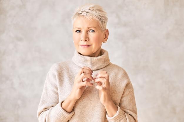 Mooie ongerust gepensioneerde vrouw, gekleed in gezellige trui en kort kapsel