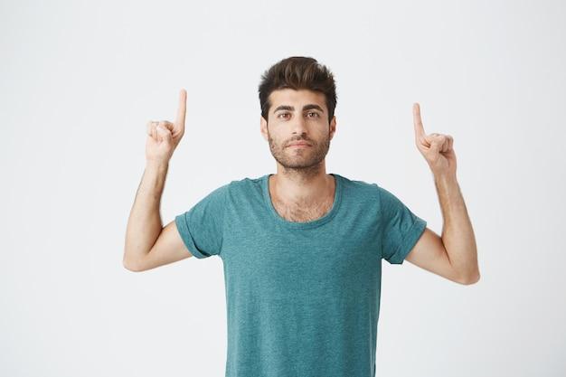 Mooie ongeschoren blanke man met ernstige uitdrukking, in casual blauw t-shirt, wijzend met de vingers op de blinde muur. ruimte voor reclame kopiëren.