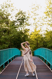 Mooie ontspannen blonde jonge vrouw gekleed in jurk, poseren in beweging op de brug.