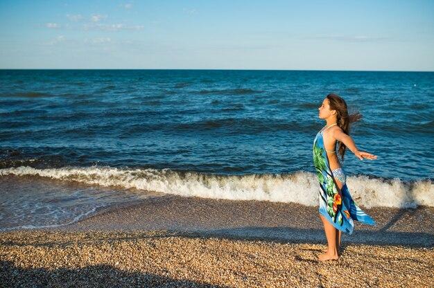 Mooie ontspannen vrouw rusten op het strand aan zee met een sjaal op een zonnige warme zomerdag.
