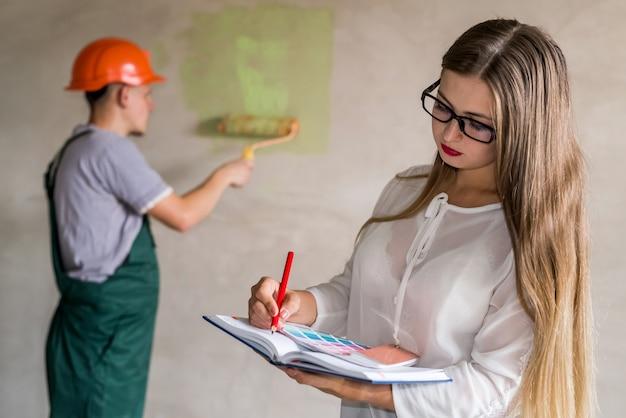 Mooie ontwerper schrijft in notitieblok terwijl werknemer muren schildert
