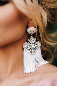 Mooie oorbellen aan de bruid, mooie nek, stijlvol kapsel.