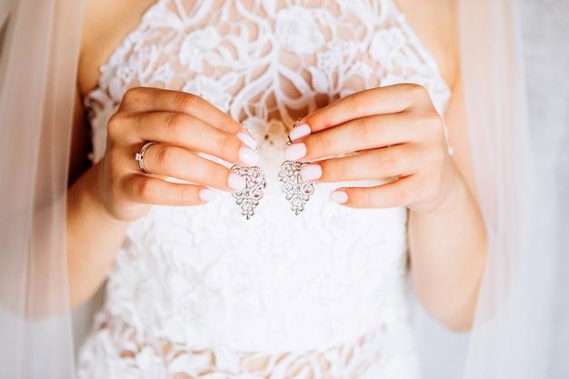 Mooie oorbellen op de palm van de bruid