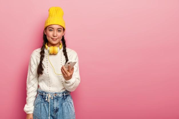 Mooie oosterse tienermeisje maakt gebruik van koptelefoon aangesloten op de mobiele telefoon, luistert naar muziek