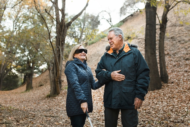 Mooie opa die zijn blinde vrouw meeneemt voor een wandeling