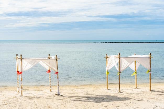 Mooie openlucht tropische strand overzeese oceaan met paraplustoel en zitkamerdek rond daar op witte wolken blauwe hemel