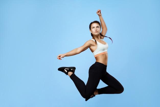 Mooie, opgewonden fitness vrouw in kleurrijke sportwear hoog springen