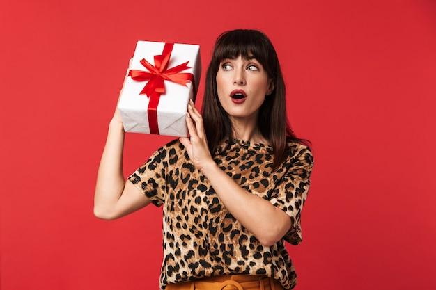 Mooie opgewonden geschokte jonge vrouw gekleed in een met dieren bedrukt shirt poseren geïsoleerd over rode muur met huidige doos.