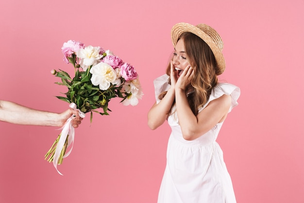 Mooie opgewonden jonge blonde meid met een zomerjurk die over een roze muur staat en een boeket pioenrozen cadeau krijgt
