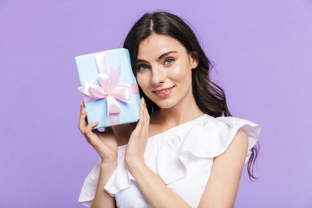 Mooie opgewonden jonge brunette vrouw staande geïsoleerd over violette muur, met huidige doos