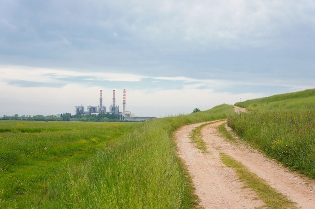Mooie opname van een groen veld aan de kant van een onverharde weg met een gebouw en een bewolkte hemel