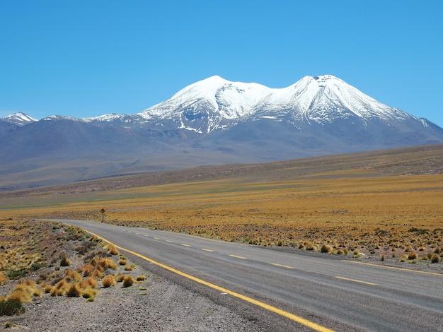 Mooie opname van een lege weg omringd door velden en bergen die overdag bedekt zijn met sneeuw