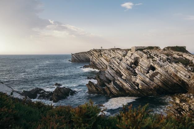 Mooie opname van een met struiken bedekte kustlijn met gekantelde zandstenen rotsformaties in peniche