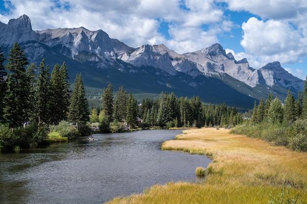 Mooie opname van een rivier door het dorp omringd door heuvels, bergen en groen