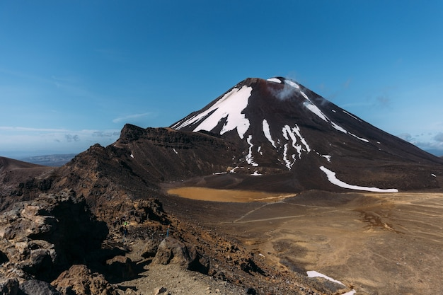 Mooie opname van een rotsachtig landschap met heuvels op de achtergrond onder een blauwe lucht