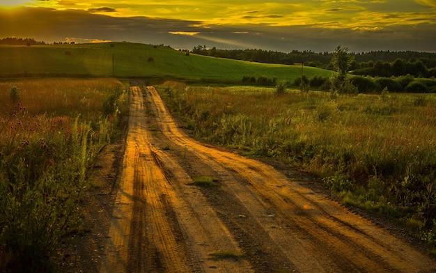 Mooie opname van een weg door het veld tijdens de prachtige zonsondergang