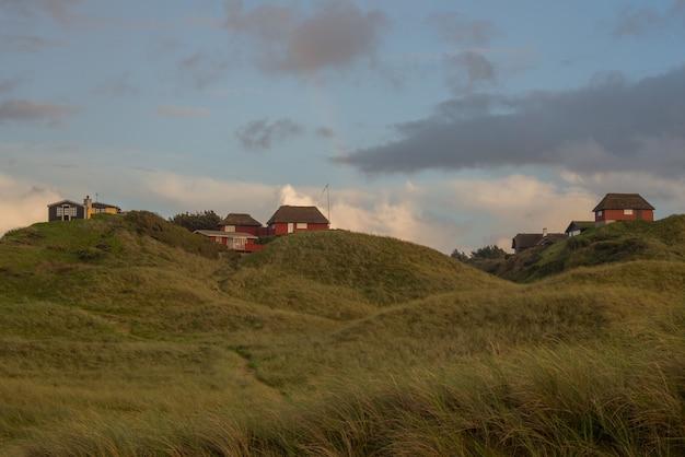 Mooie opname van huizen bovenop heuvels met dunne wolken