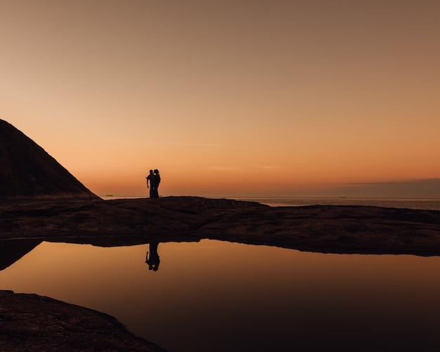 Mooie opname van silhouetten van mensen op een strand tijdens zonsopgang