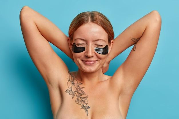 Mooie oprechte vrouw met sproeten houdt de handen achter de nek, sluit de ogen, past zwarte collageenpleisters toe, geniet van verjongingsprocedure, gezichtsverzorgingsproduct, staat topless met tatoeage op lichaam