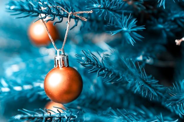 Mooie oranje decoraties op een kerstboom.