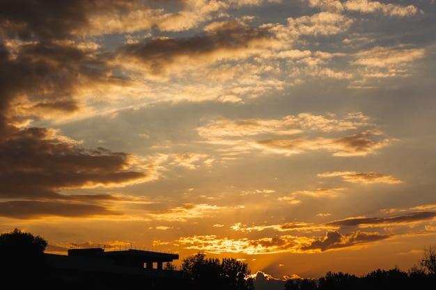Mooie oranje zonsonderganghemel over kleine stad. donkere silhouetten van gebouwen in de schemering.