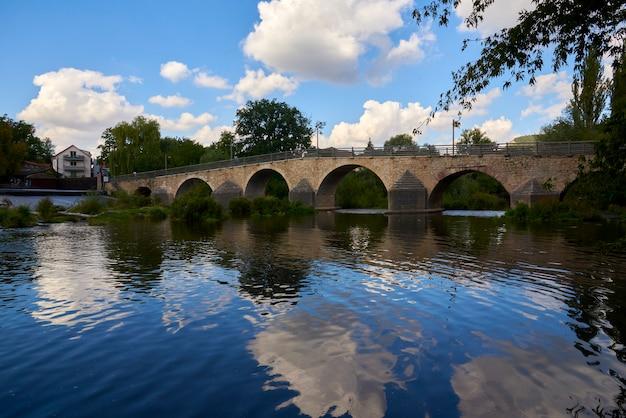 Mooie oude brug over een kalme rivier op een zonnige dag