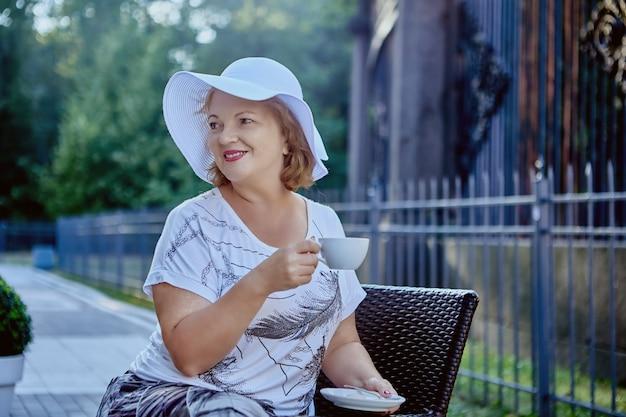 Mooie oude gelukkige vrouw in hoed drinkt koffie in het park