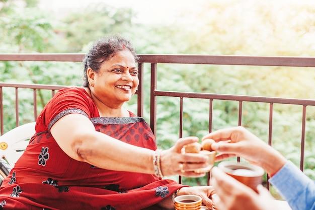 Mooie oude indiase vrouw die traditionele zoetigheden aanbiedt aan de gast