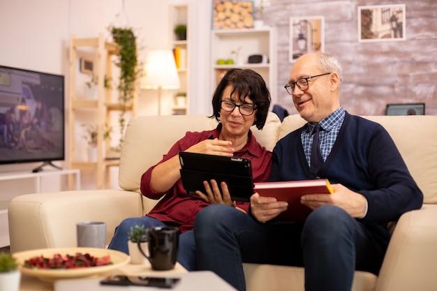 Mooie oude paar met behulp van een digitale tablet om te chatten met hun familie. ouderen die moderne technologie gebruiken