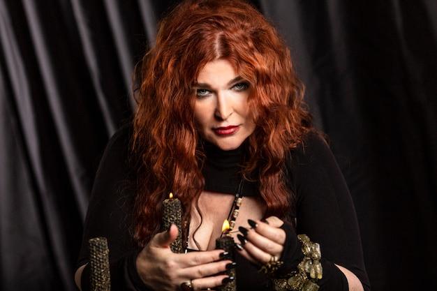 Mooie oude roodharige vrouw waarzegster voert een magisch ritueel uit.