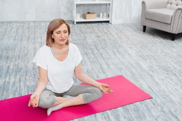 Mooie oude vrouw die op yogamat thuis mediteren