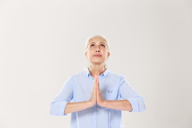 Mooie oude vrouw die voor vrede bidt, die stijgend kijkt