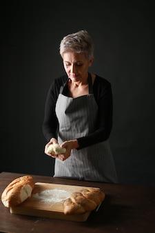Mooie oude vrouw in een schort bereidt vers brood van deeg