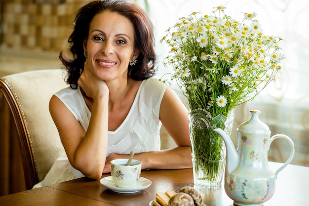 Mooie oude vrouw in een witte blouse zittend aan een ronde tafel met een boeket madeliefjes Premium Foto