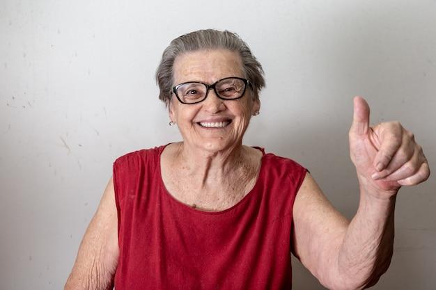 Mooie oude vrouw met twee tumbs omhoog. vrolijke kaukasische oudste die twee duimen op witte achtergrond toont.