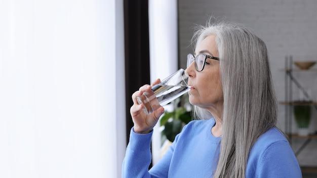 Mooie oudere grijsharige vrouw die glas water vasthoudt en drinkt.