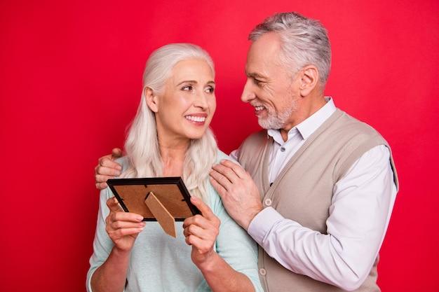 Mooie oudere paar poseren samen tegen de rode muur
