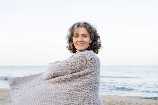Mooie oudere vrouw die geniet van haar tijd op het strand