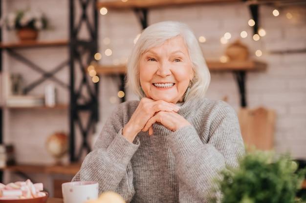 Mooie oudere vrouw in grijze trui met een geweldig gevoel
