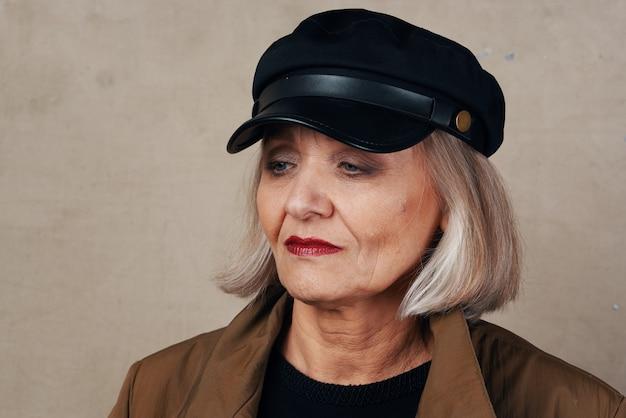 Mooie oudere vrouw in jas zwarte hoed mode
