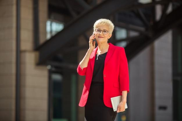 Mooie oudere vrouw in leeftijd met een kort kapsel en een bril in een rode jas met een telefoon