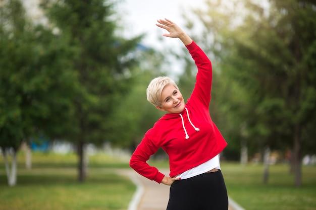 Mooie oudere vrouw met kort kapsel gaat sporten in het park