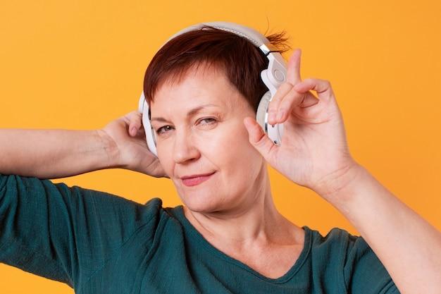 Mooie oudere vrouwelijke muziek luisteren