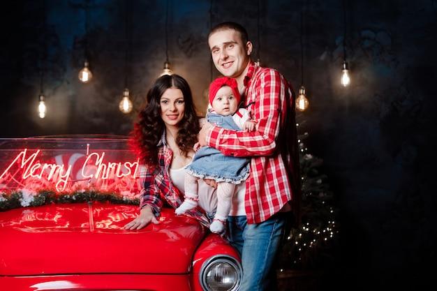 Mooie ouders houden hun kleine schattige dochter in hun armen met plezier in de buurt van retro auto in de studio. kerst familie look. nieuwjaars landschap.