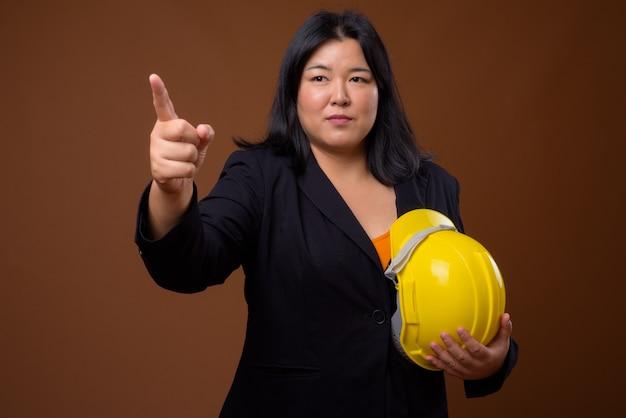 Mooie overgewicht aziatische zakenvrouw bedrijf hardhat op bruin