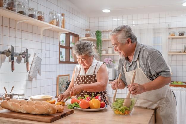 Mooie paar aziatische ouderling blij en lachend koken salade samen voor ontbijt thuis keuken