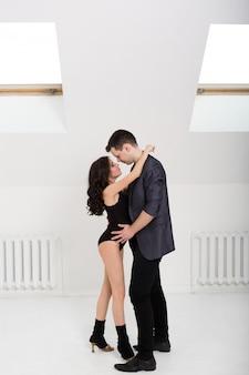 Mooie paar bachata dansen op witte achtergrond in de studio